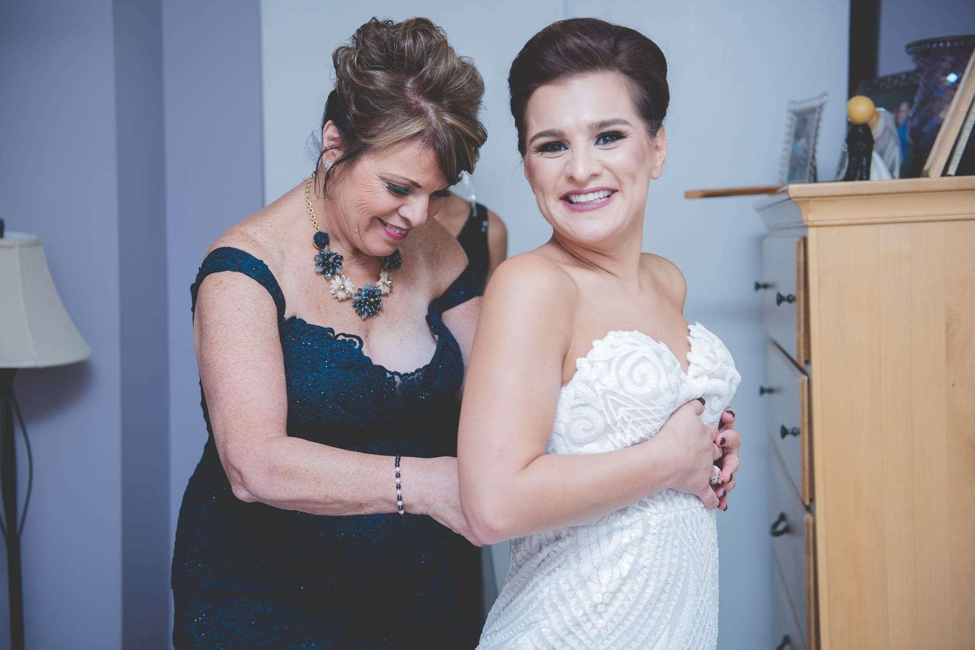 bride getting into wedding dress Jennifer's bridal Hayley Paige dress