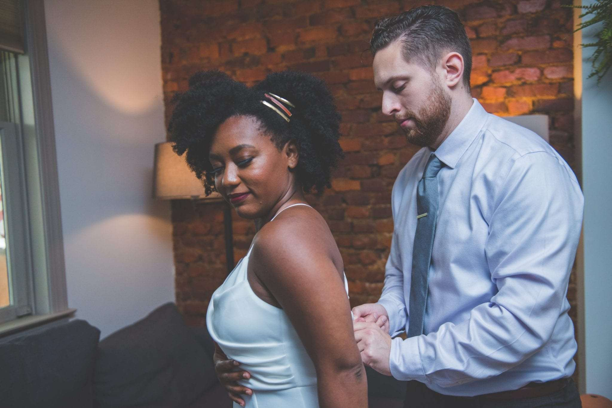 Groom helping bride get ready NJ wedding photographer